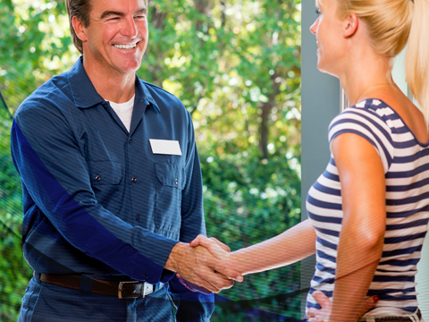 A technician and a homeowner shaking hands